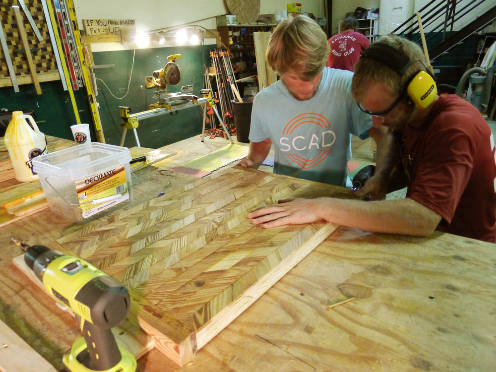 Shop crew Tim McCarthy and Brett Egger assembling our mosaic pattern on the two top tables.