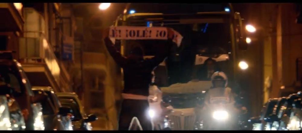 """Un aficionado muestra una bufanda con el texto ¡OLÉ! a un supuesto autobús del Barça mientras grita """"¡Viva España!""""."""