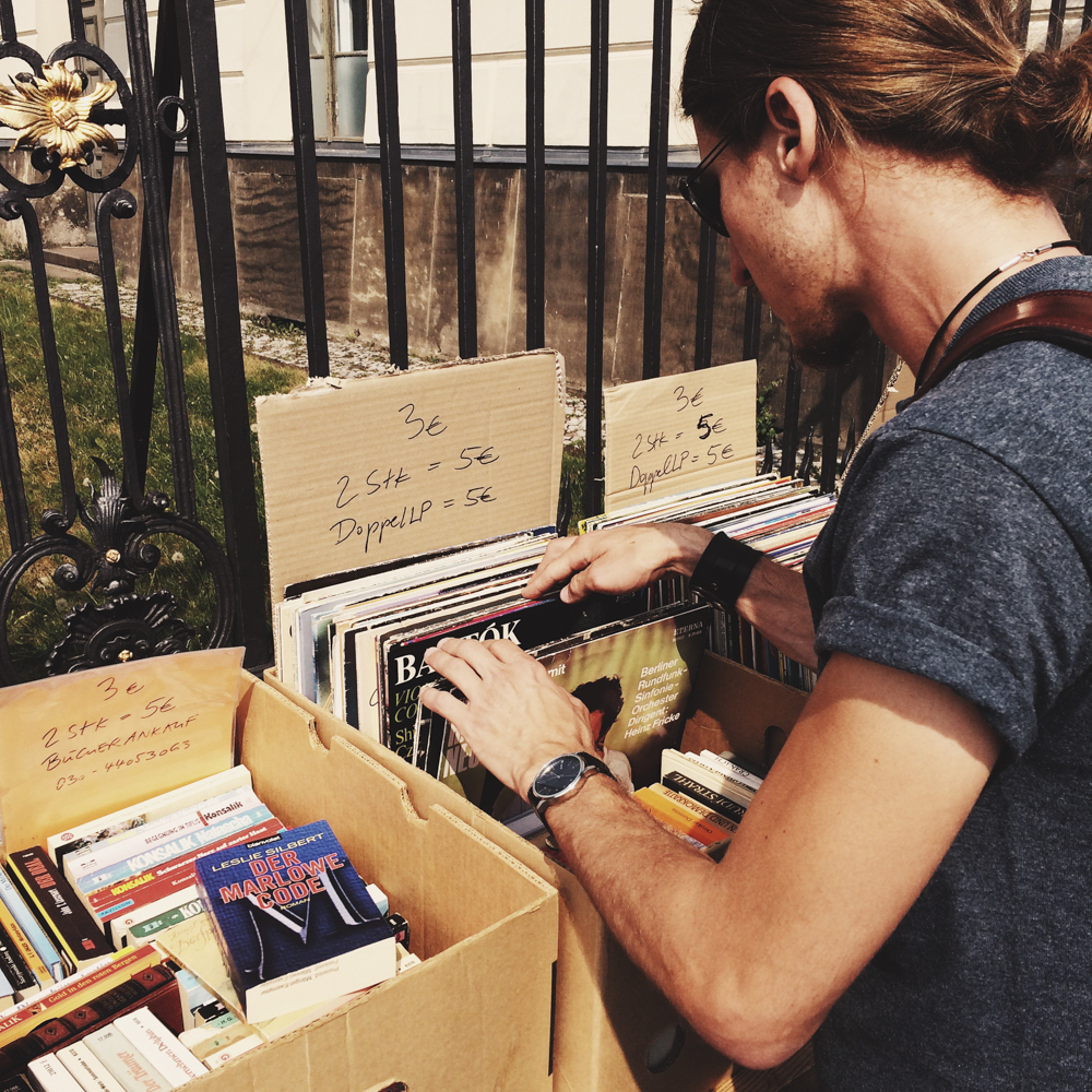 Markets on the side of the road with boxes full of classical music records.