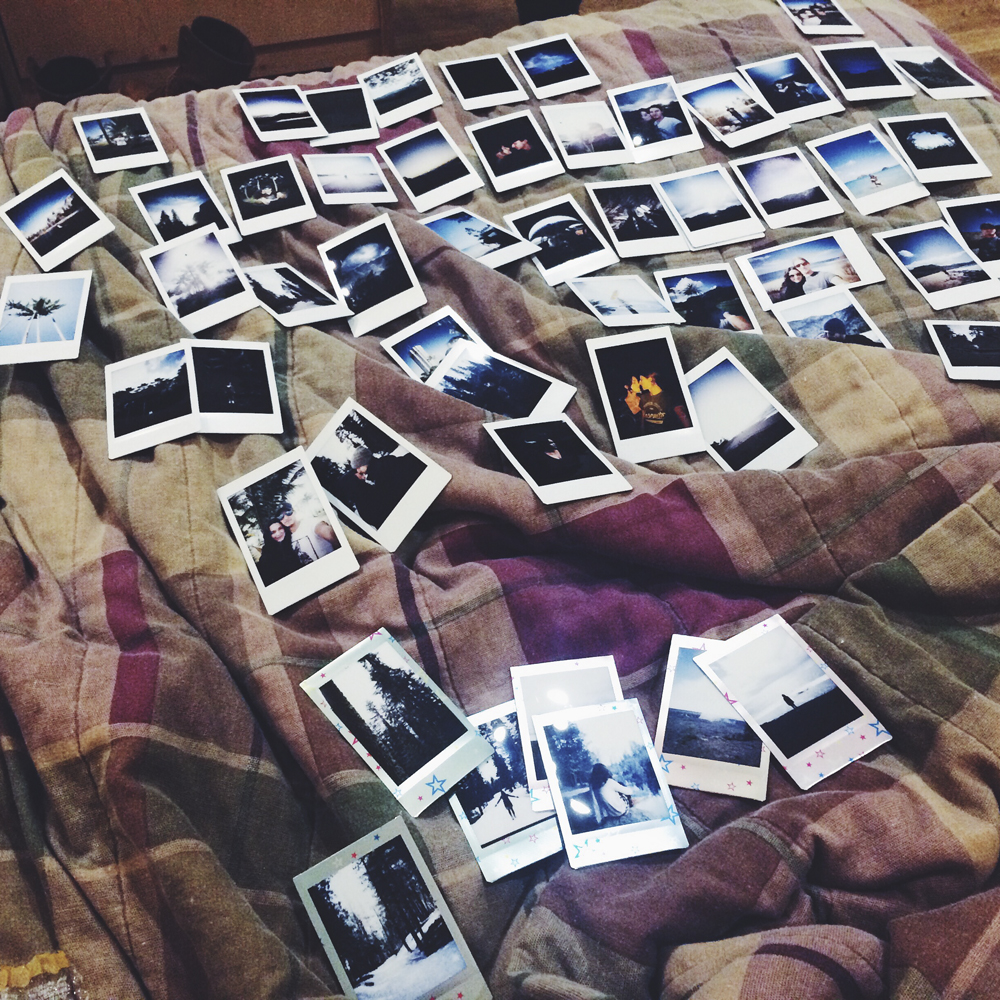 All our polaroids laid out on our bed in our cabin.