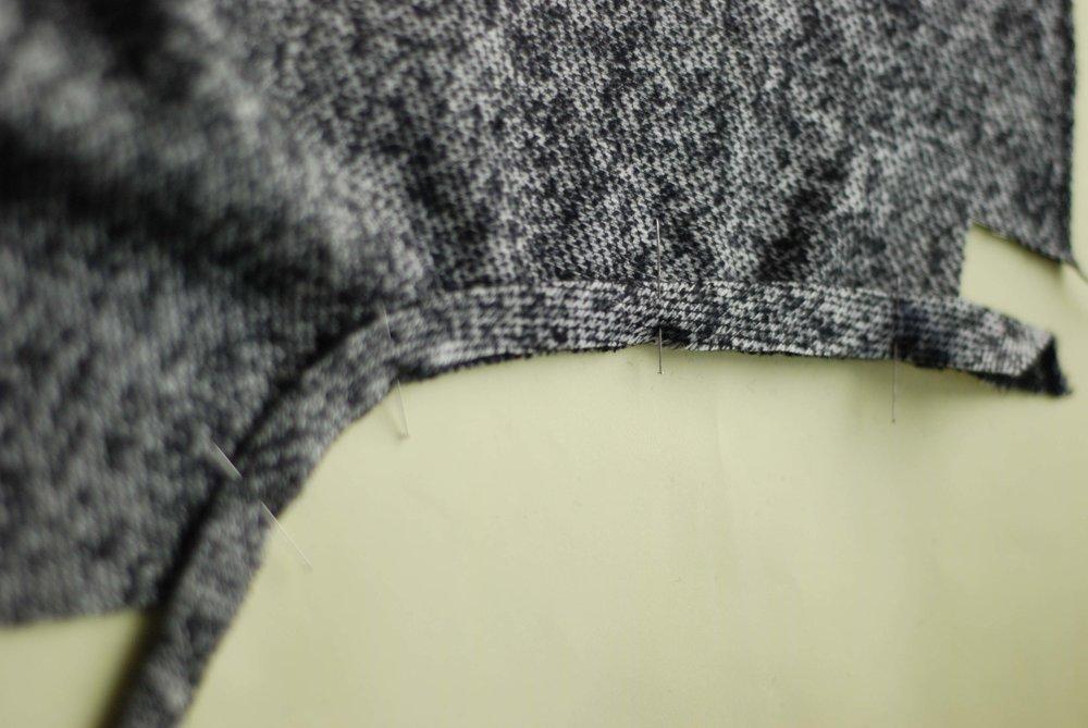 Placer det foldede kantebånd langs ærmegabet