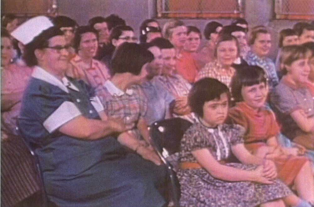 "At Sunday church service in the gym. Note the short ""pudding basin"" institutional haircuts on the girls. Photo courtesy Archives of Ontario."