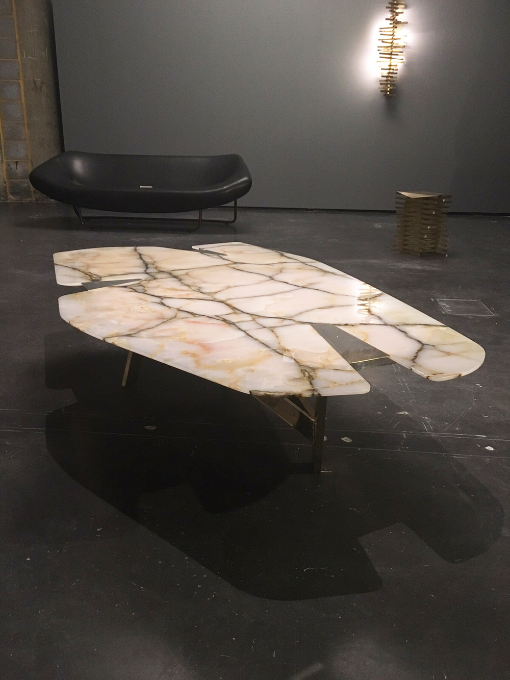 Onyx table with reverse knife edge detail, sculptural sofa and aged brass side table.
