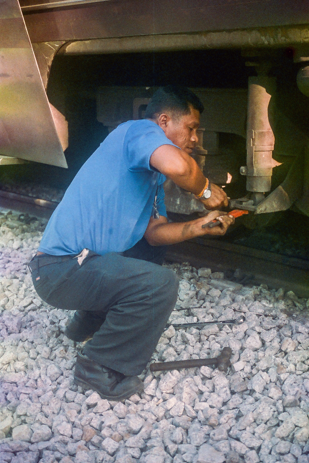 Conductor fixing the train on the Georgetown to Chumphon route.