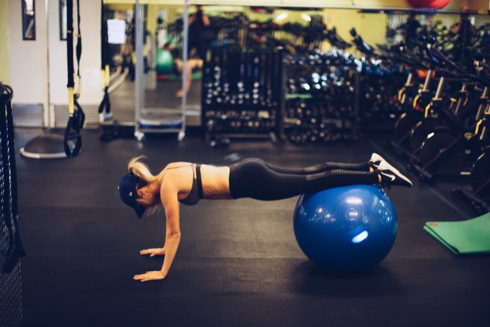 Start in plank position with your shins on medicine ball.