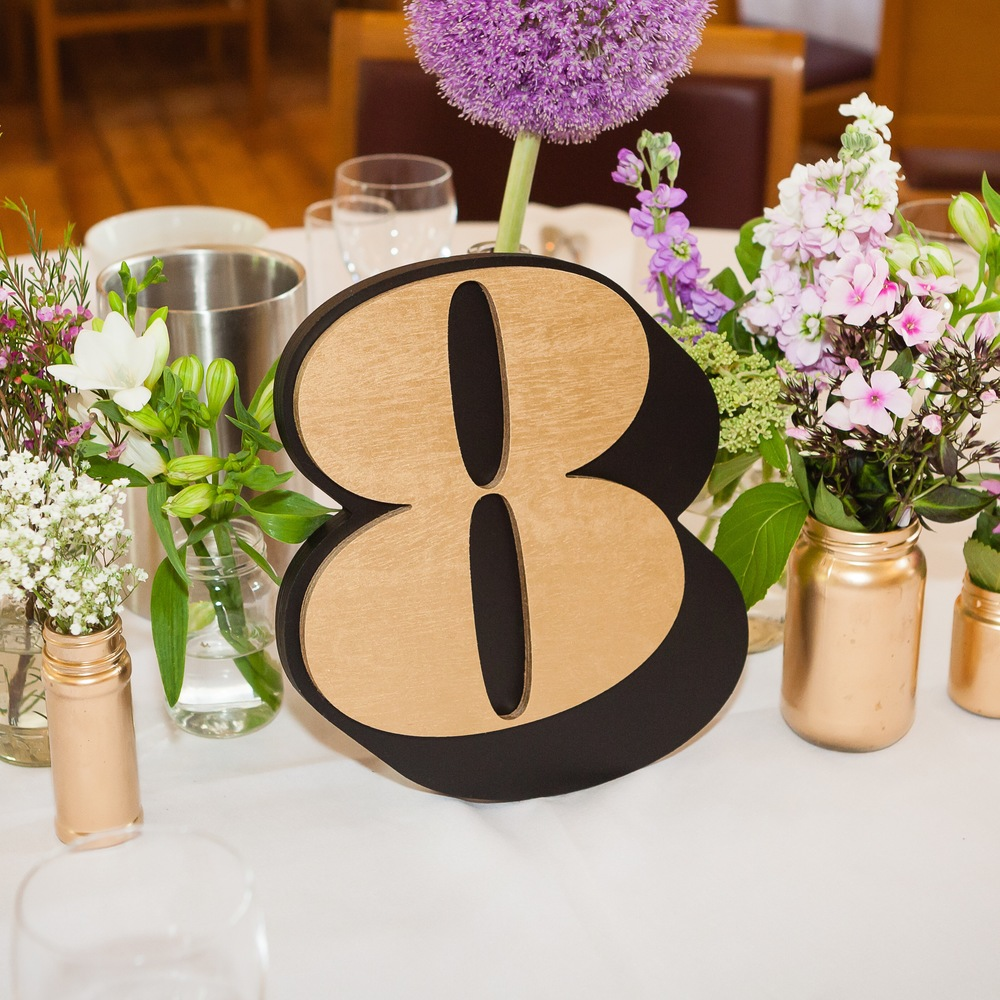 Our table numbers were custom laser-cut pieces of wood, which we sandwiched together and glued a wedge on the back as a stand. We spraypainted the 'shadow' black and the front number gold. The typeface was House Industries 'Worthe Numerals'