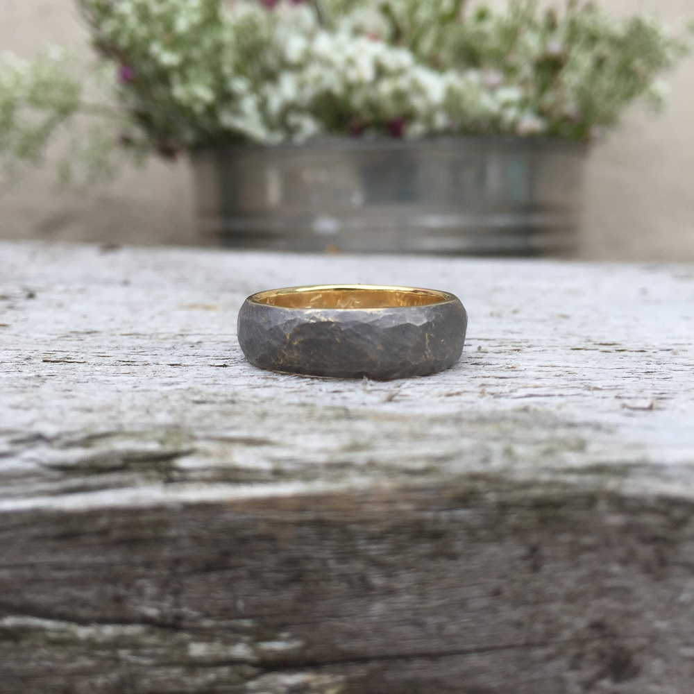 My wedding ring was designed & made by my wife Janey. It's 18-carat yellow gold with black rhodium plating. It's hand-hammered matte texture on the outside, with polished gold on the lip & inside. It features a custom engraving on the inside of the band, with a very special hidden diamond on the inside of the ring! I absolutely adore it!
