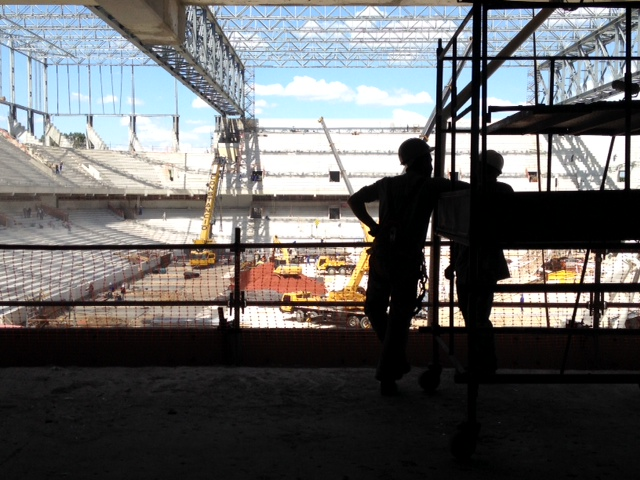 Workers look out at construction site at Arena da Baixada stadium in Curitiba, Brazil