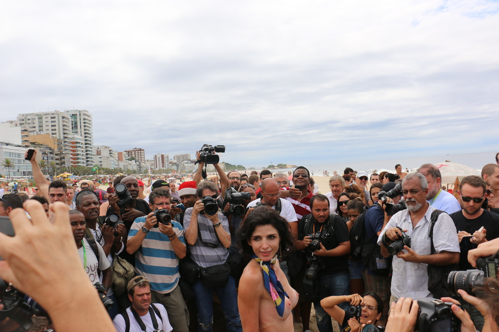 Ana Paula Nogueira, 34, is surrounded by press as she goes topless on Ipanema Beach during Toplessaço protest
