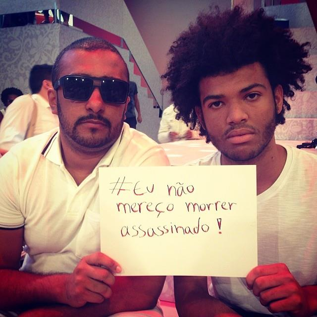 Complexo do Alemão community activist Rene Silva (right) with sign (Posted to Facebook by Rene Silva - 04/27/14)