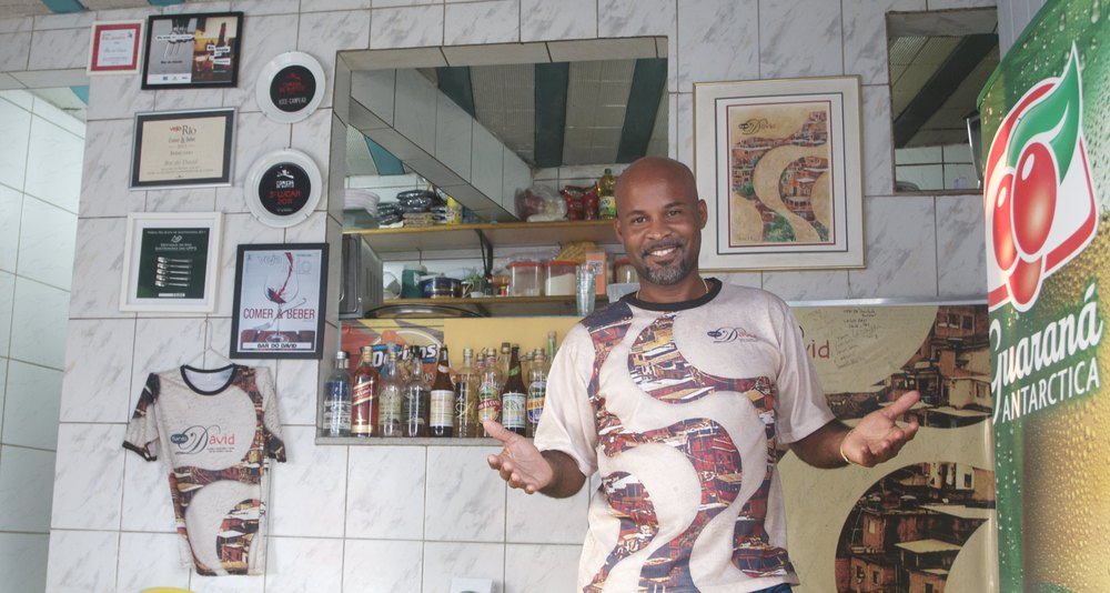 "David Viera Bispo, owner of ""Bar do David"" proudly displays his awards on the wall of his restaurant in Chapéu Mangueira favela (Photo by Flora Charner)."