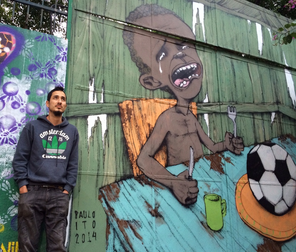 Street artist Paulo Ito stands in front of his mural that became a viral sensation and a symbol of protest against the upcoming 2014 FIFA World Cup tournament (Photo by Flora Charner)