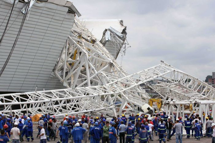 Workers stare at damages after a crane fell across part of the metallic structure at the Arena de Sao Paulo - December 2013 (Source: AFP)