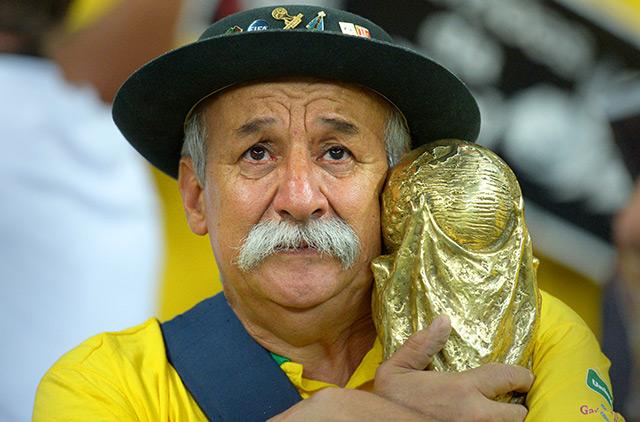 Fan clings on to World Cup trophy replica in Belo Horizonte (Source: EPA)