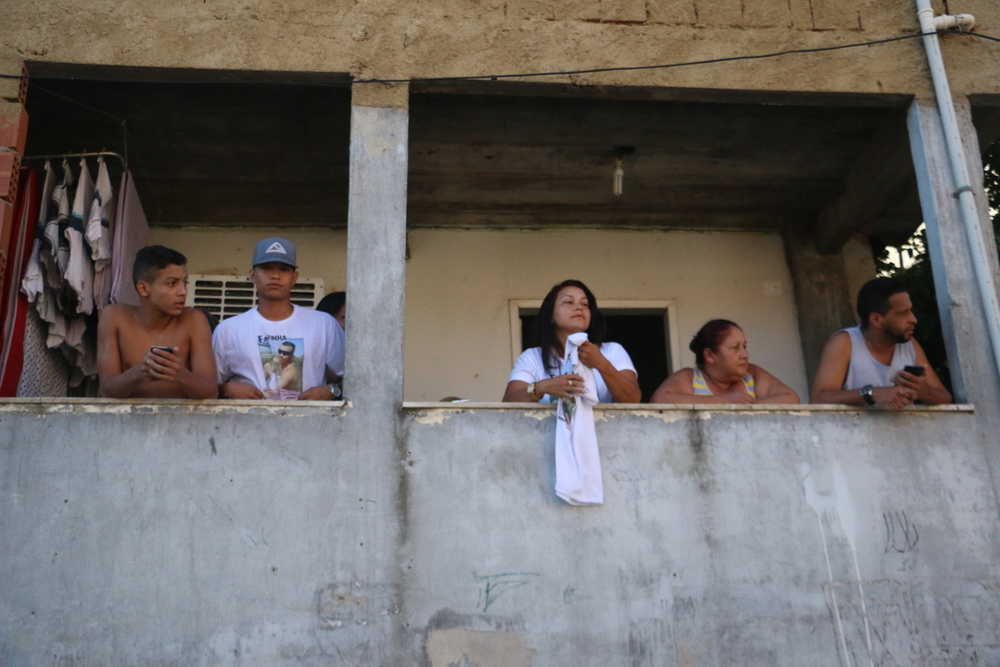 "Relatives of a man Rodrigo dos Santos, known as ""Farinha,"" who was also killed last week hold t-shirts from balcony. According to police, Farinha was found armed. Family denies his involvement with the local drug trafficking ring. Others residents refused to confirm or deny his involvement. Photo by Flora Charner"