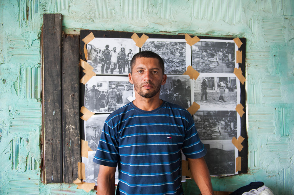 Now homeless, Jose Luis stands in front of photographs attesting to the violent eviction he and his community of Alto de Paz experienced.  Deborah Espinosa for The World Justice Project.