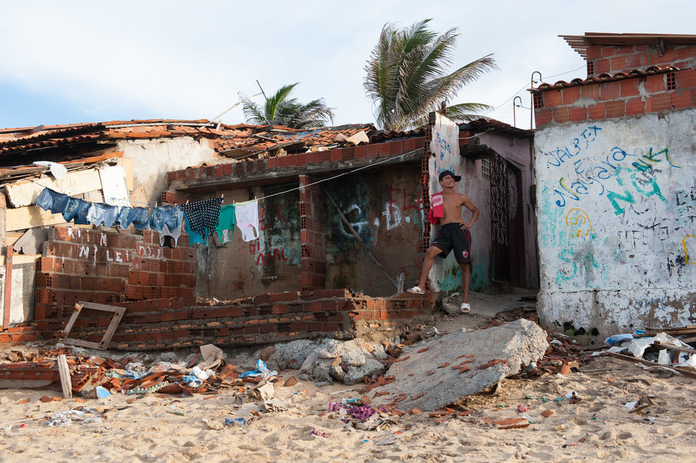 A young man stands outside his home in   the beachside City of Fortaleza, Brazil. Fortaleza is one of several cities to host the 2014 World Cup and the 2016 Olympics. As the excitement for the World Cup builds, Fortaleza's favela (slum) residents grow worried about impending eviction.