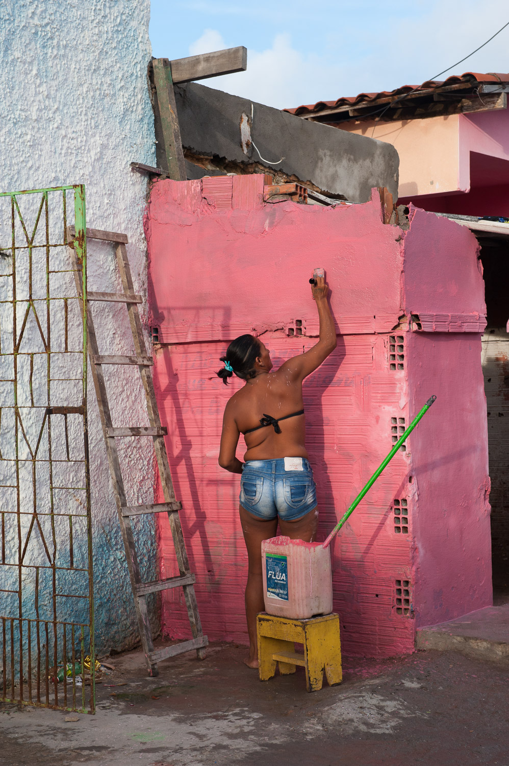 "In defiance, some favela residents paint over the ""X"" tag that the City of Fortaleza uses to indicate that a home will be demolished."