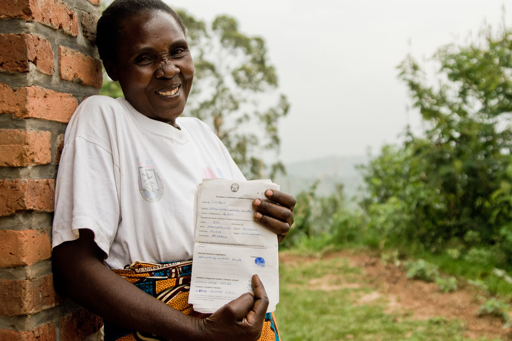 Berta, a Rwandan widow and mother of eight proudly displays her newly issued documents showing that she owns her land.  The documents are so precious to her, she keeps them with her in the pocket of her skirt.