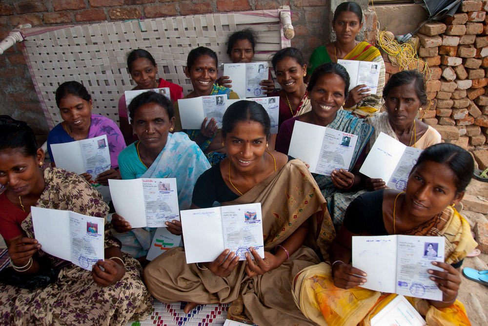 in Andhra Pradesh, India, a   group of formerly landless women   display their new pattas (titles) showing that each owns one acre of land. The women had participated   in a World Bank Land Purchase Program, which subsidized the purchase of land on the open market for landless women. The project required that the land be registered in the name of the woman only.