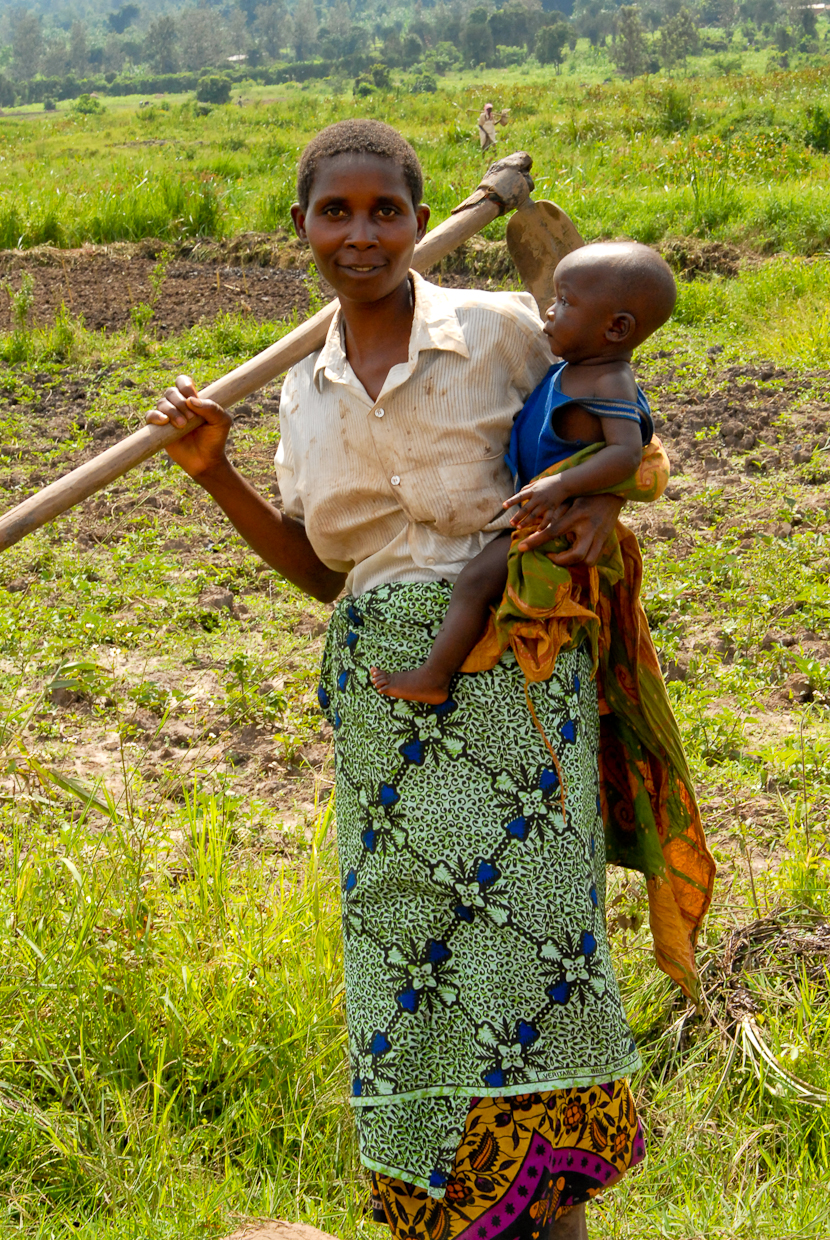 Consolata, with her son in tow, farm land that they lease from the government.
