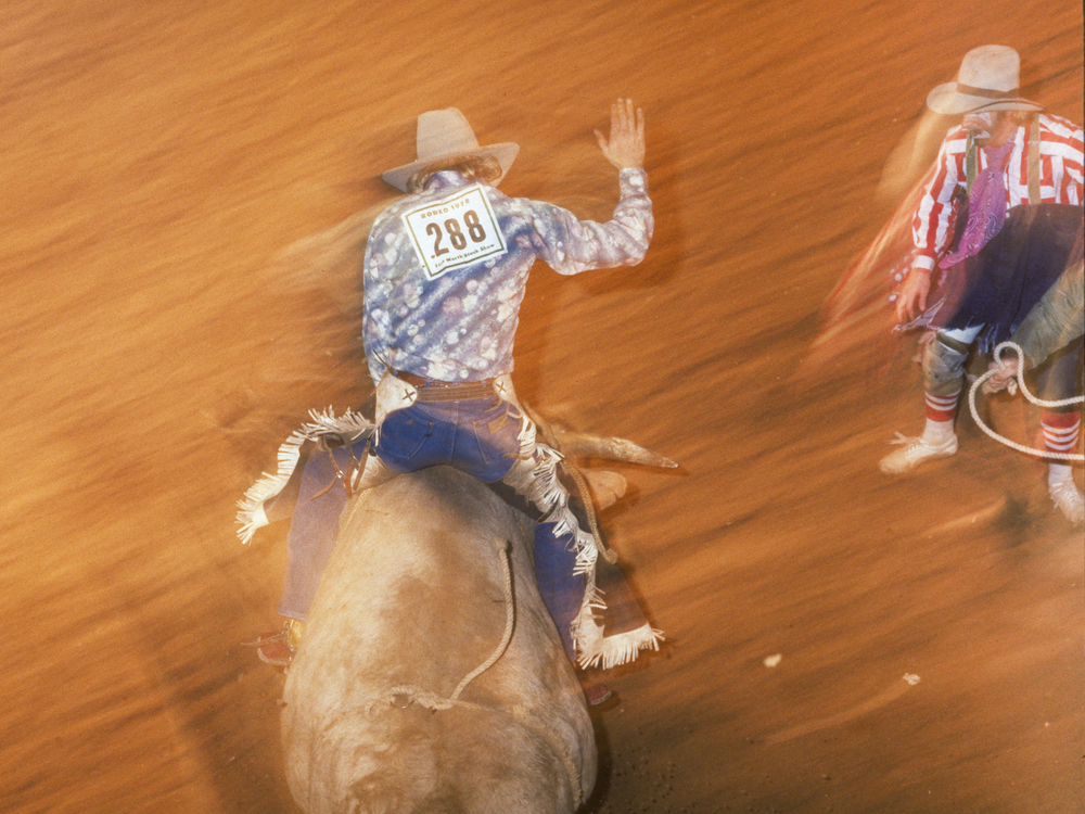 Strobe light and long shutter special effect add dynamic element to bull-rider #288 and rodeo clown at Fort Worth Fat Stock Show & Rodeo.