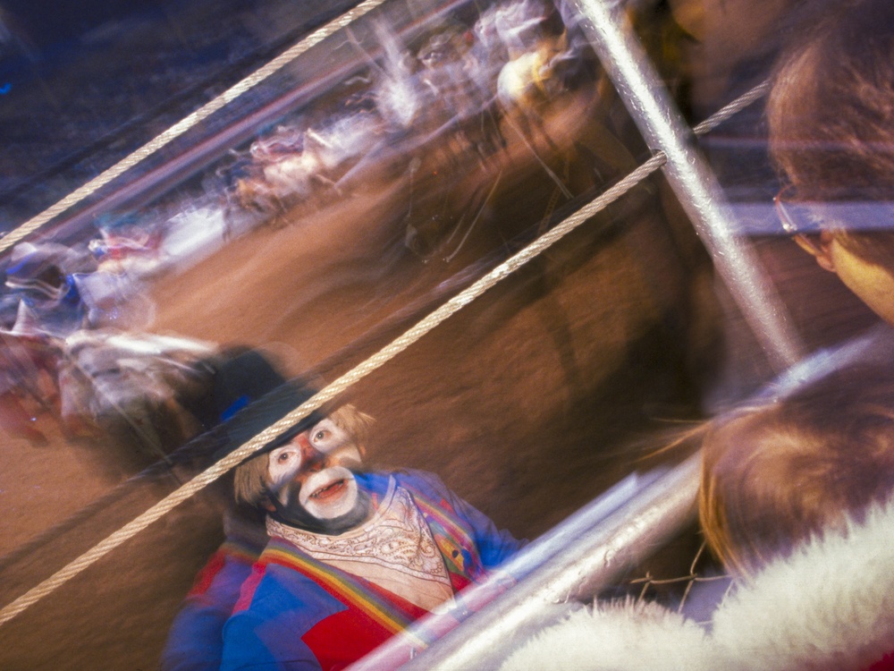 Strobe light and long shutter special effect add dynamic element to image of rodeo clown and his audience.