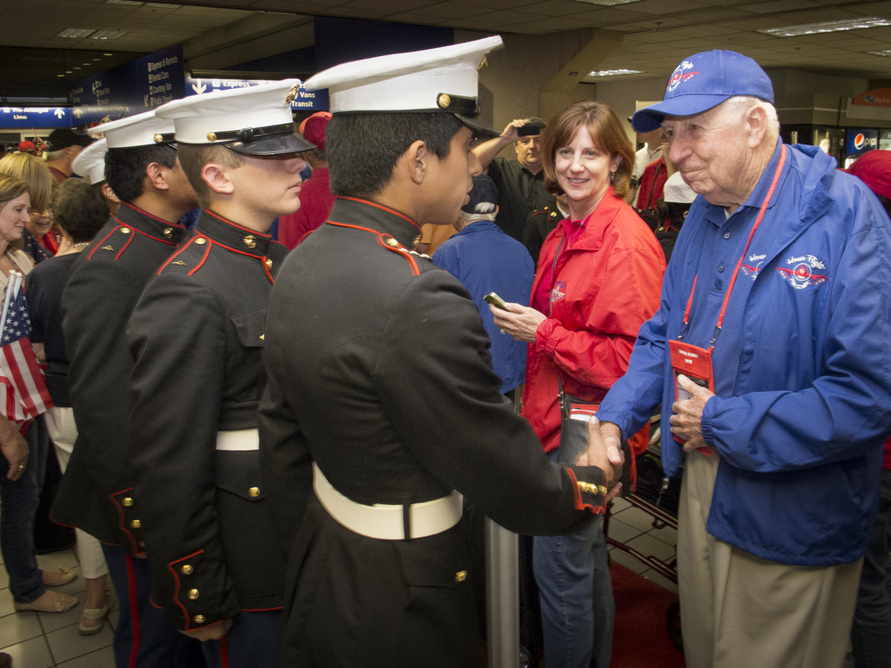 Honor Flight participant and WWII verteran, Captain Bill J Baker (Ret.) receives congratulations from young Marines at his return from the Washington, DC trip and tour. Copyright © Kipp Baker, All rights reserved.