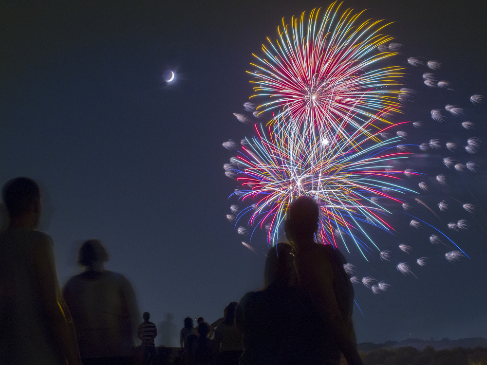 A crescent moon smiles on July 4th fireworks, Fort Worth, TX, USA. Copyright © Kipp Baker, All rights reserved.