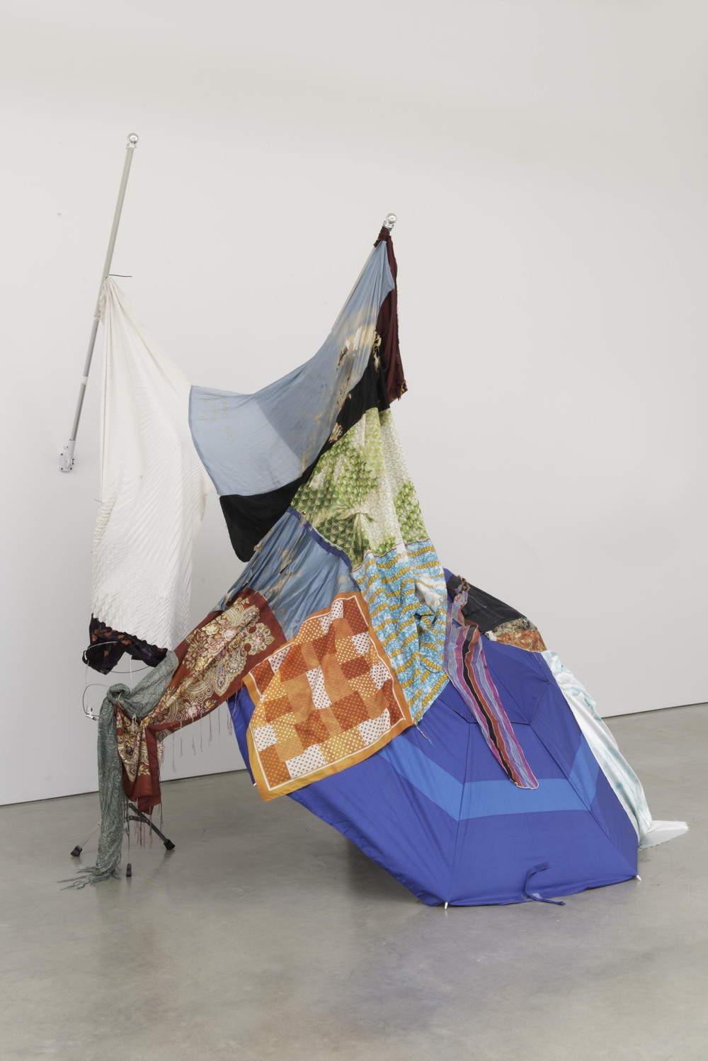Eric Mack Newdaline 2016 Two flagpoles, umbrella, silk, cotton, polyester, aluminum, wood, zip ties, and straight pins 108 x 102 x 92 in (274.32h x 259.08w x 233.68d cm) ENM001