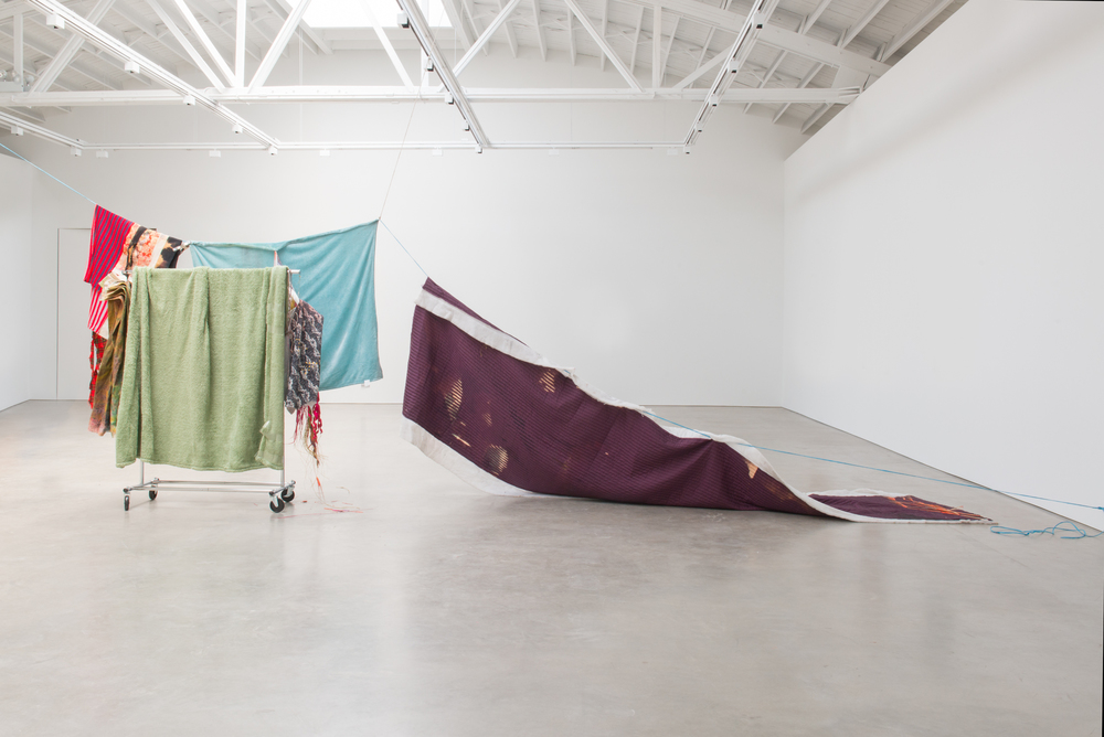 Eric Mack  Come Live With Me Angel  2016 Rope, straight pins, acrylic on plush microfiber blankets, polyester fabrics, dye, bleached silk, decorative bouquet, and aluminum clothing rack 94h x 300w x 52d in ENM002