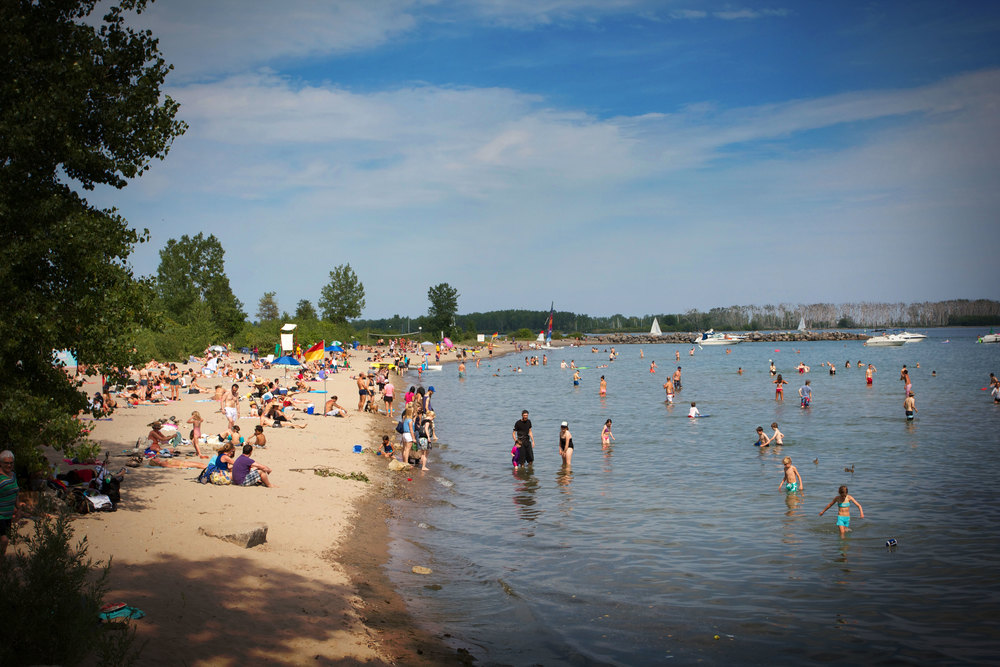 Torontonians embracing Ward's Island Beach. (Photo via Lake Ontario Waterkeeper)