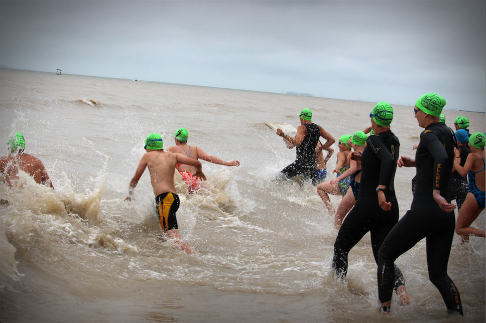 Swimmers bounding into Lake Erie's chilly waters for the North Shore Challenge. (Photo via Lake Ontario Waterkeeper)
