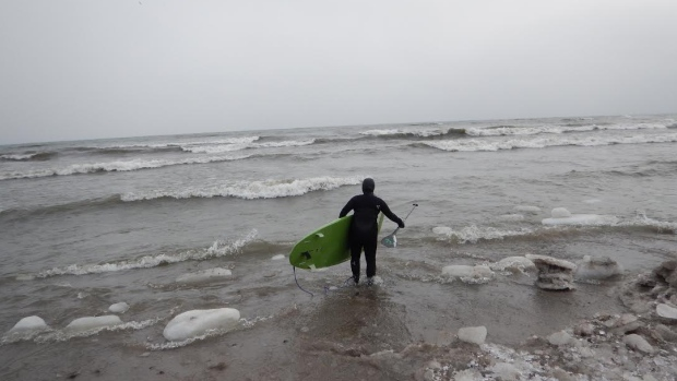 A paddlerboarder wading into Lake Ontario's chilly waters. (Photo by Robin Pacquing)