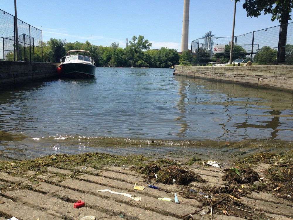 Sewage debris (such as condoms and tampon applicators) found at a boat launch. The smokestack from Ashbridges Wastewater Treatment Facility can be seen in the background. (Photo by Claire Lawson)