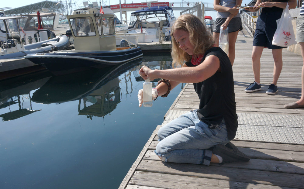 Volunteer, Oksana sampling water from Toronto's Pier 4. (Photo by Lake Ontario Waterkeeper)