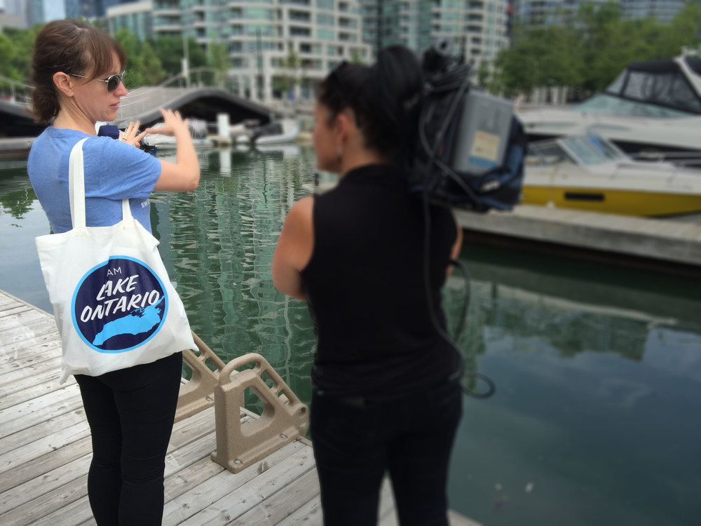 Waterkeeper Vice-President, Krystyn Tully talks to CityTV about the sewage pollution found in Toronto's inner harbour. (Photo by Lake Ontario)..