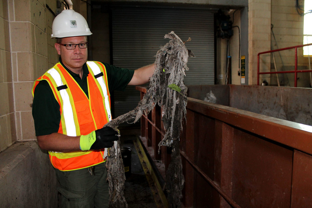 "Barry Orr holding up a ""rope"" of wipes and other non-flushables that were pulled out of wastewater. (Photo by Ruby Pajares)"