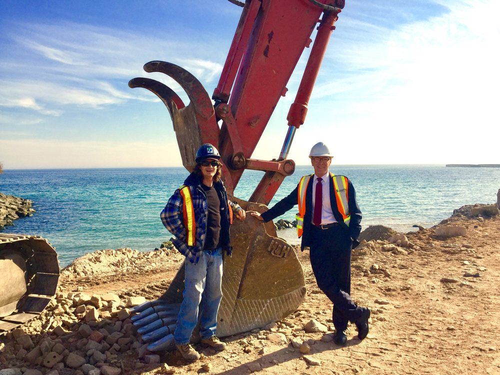 Councillor Jim Tovey on-site as first load of rubble is placed to construct Peel Region's new waterfront conservation area. Left to right: Andy Brown, Heavy Equipment Operator; Jim Tovey, Councillor, Mississauga Ward 1.