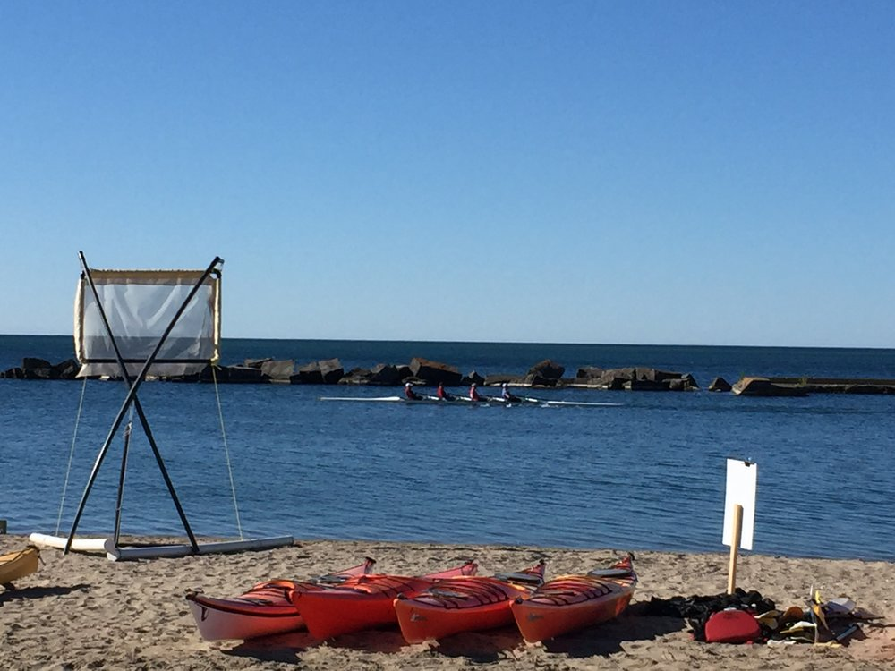 Group of four rowing alongside Sunnyside Beach in Toronto. Photo by Lake Ontario Waterkeeper.