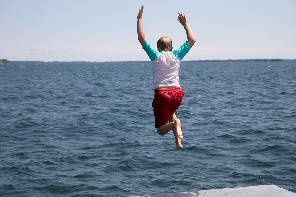Leaping from the Gord Edgar Downie Pier into Lake Ontario. Photo by Swim Drink Fish.