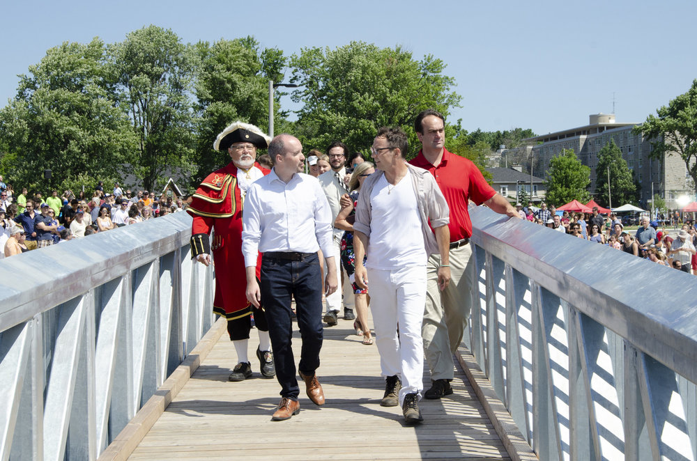 Kingston Mayor (left) and Patrick Downie (right) cross the bridge from Breakwater Park to the new Gord Edgar Downie swimming pier. July 26, 2018. Photo by Swim Drink Fish.