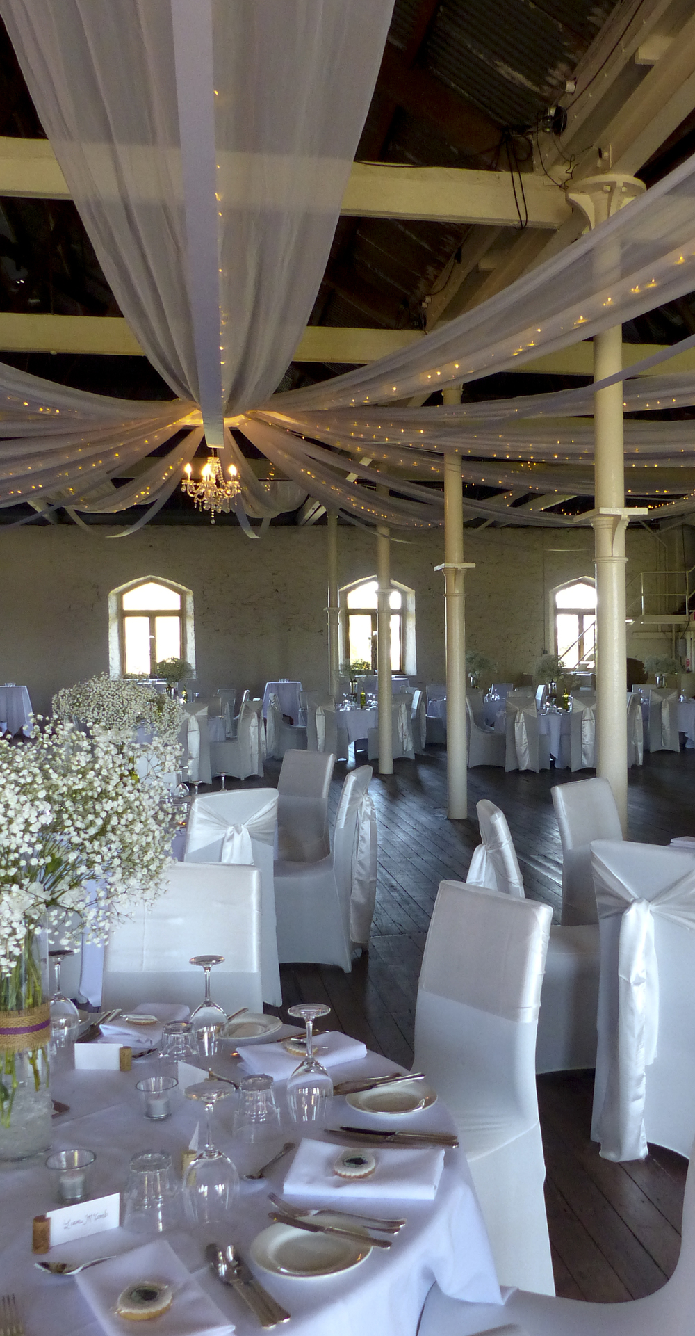 A classic 16 arm ceiling canopy with white ribbons and chandelier.