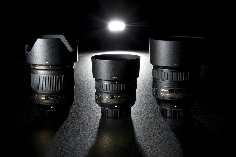 Nikon fast primes -- 28 mm f/1.8, 50 mm f/1.8, and the 85 mm f/1.8. Photo by Dustin Gaffke.
