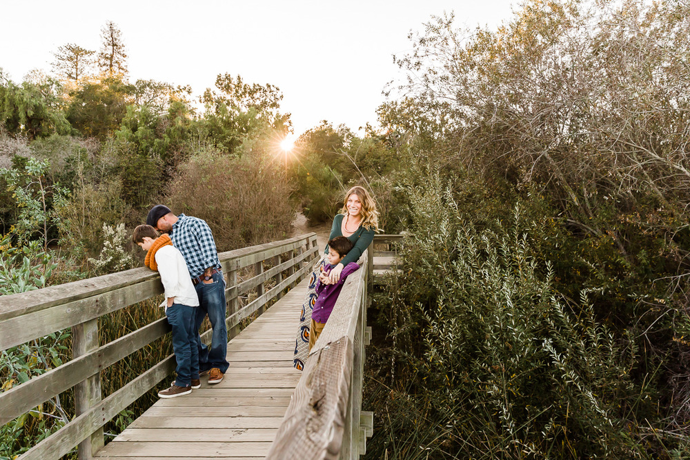 Image from a Family Session with a man, woman and their two children standing on a bridge