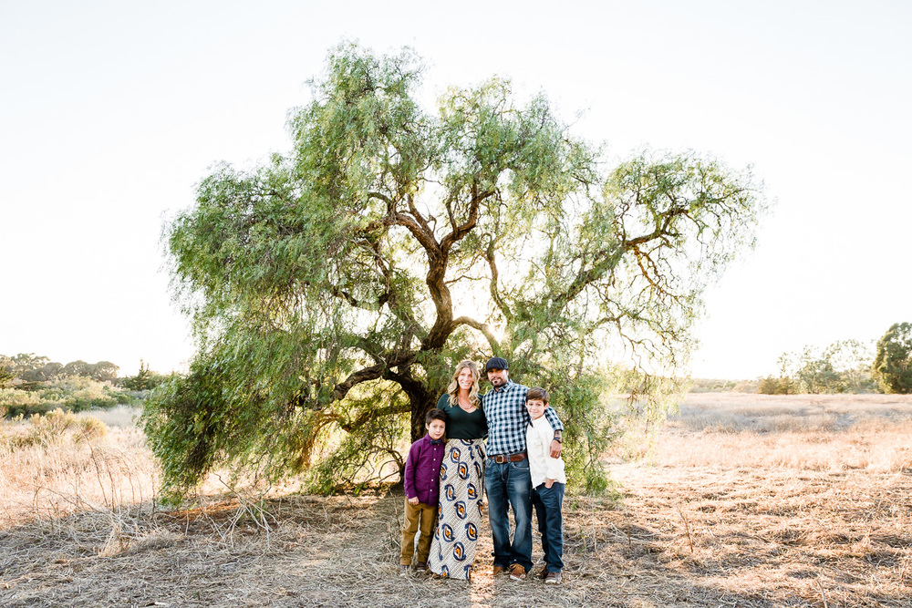 Image from a Family Session with a man, woman and their two sons standing in front of a tree