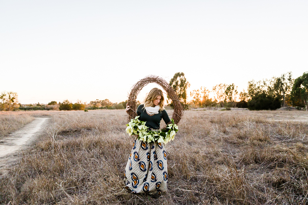 Image from a Family Session with a woman in a dry field holding a large wreath