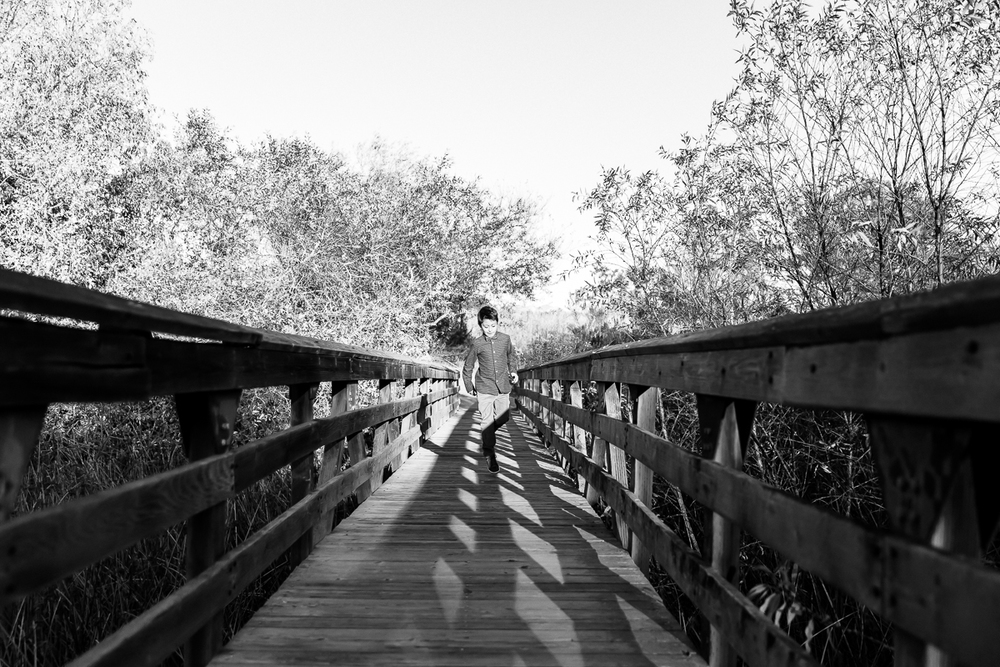 Image from a Family Session with a boy skipping across a bridge