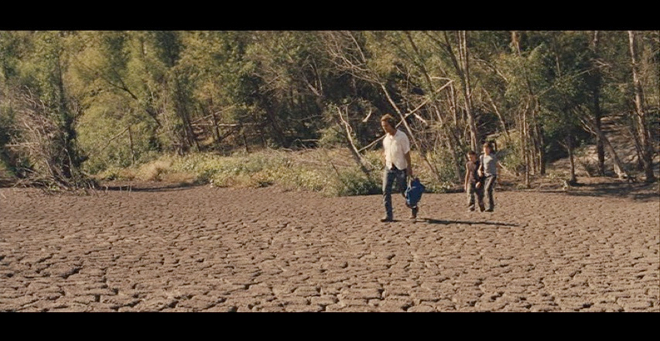 PHOTO CREDIT: Screenshot of Mud, Ellis & Neckbone walking across a dry, cracked, moon-like area on the island.