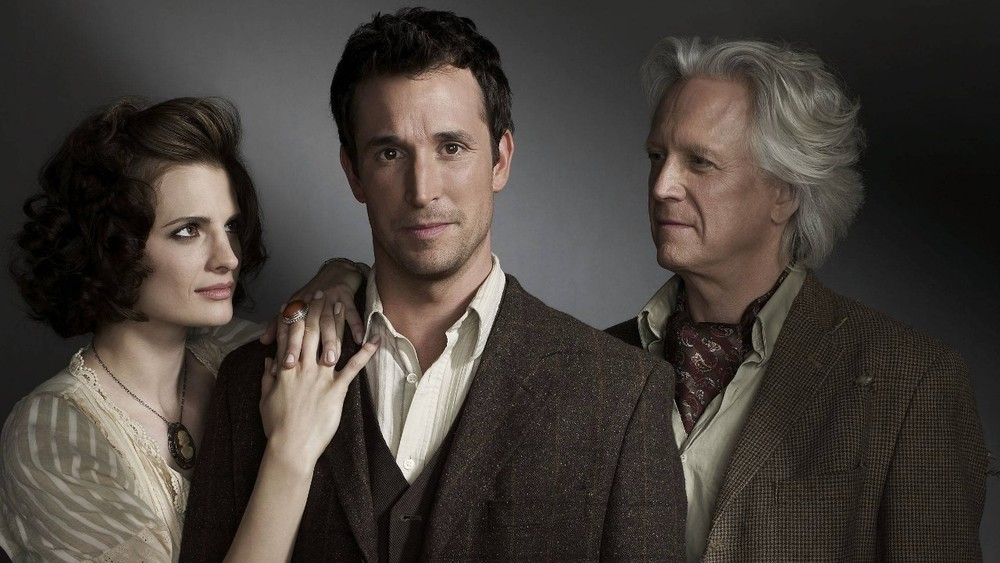 The cast of   The Librarian: Curse of Judas Chalice   (2008): Stana Katic, Noah Wyle, and Bruce Davison. Image via  Google .